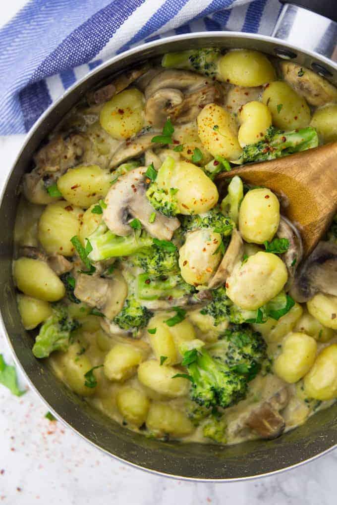 Gnocchi Pfanne mit Brokkoli und Pilzen, bestreut mit Chiliflocken und Petersilie