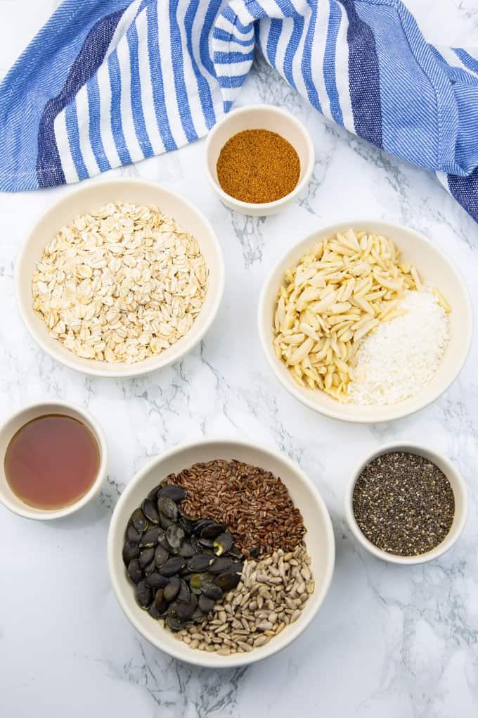 Die Zutaten zum Müsli selber machen in kleinen weißen Schüsseln auf einer Marmorplatte (Haferflocken, Zimt, Samen und Nüsse)