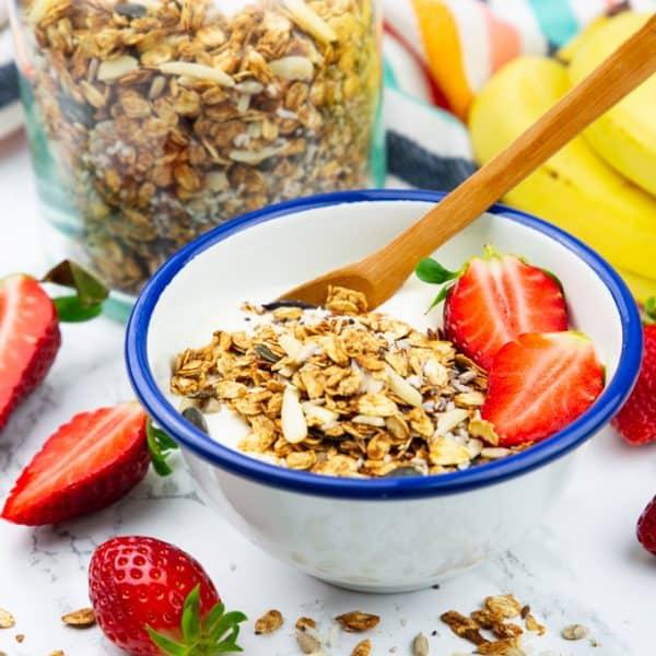 Eine Schüssel mit selbstgemachtem Müsli mit veganem Joghurt und Erdbeeren auf einer Marmorplatte