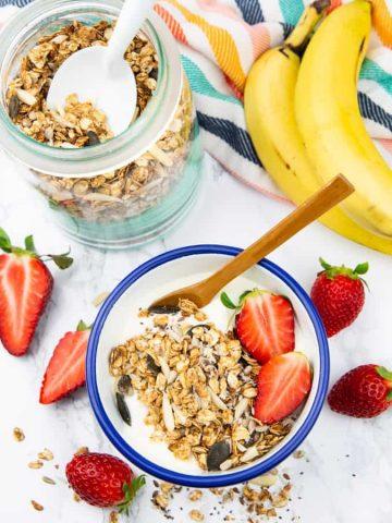 Eine Schüssel mit selbstgemachtem Müsli mit veganem Joghurt und Erdbeeren auf einer Marmorarbeitsplatte