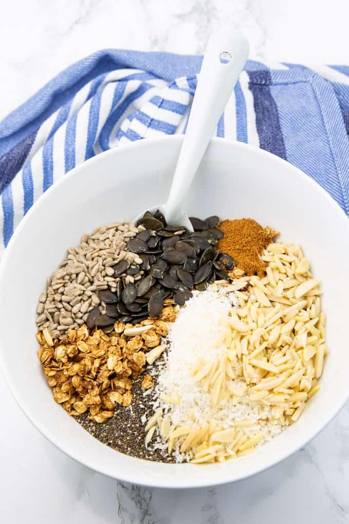 Selbstgemachtes Müsli mit Mandelsplittern, Kokosraspeln, Sonnenblumenkernen, Chiasamen in einer weißen Schüssel auf einer Marmorplatte