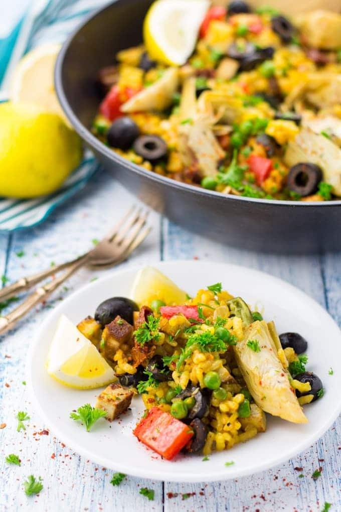 Paella auf einem weißen Teller mit einer schwarzen Pfanne mit mehr Paella und zwei Zitronen im Hintergrund