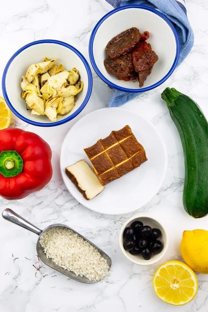 Räuchertofu, Artischockenherzen, getrocknete Tomaten, Paella Reis, eine Zucchini, eine Paprika und zwei Zitronen auf einer Marmorplatte