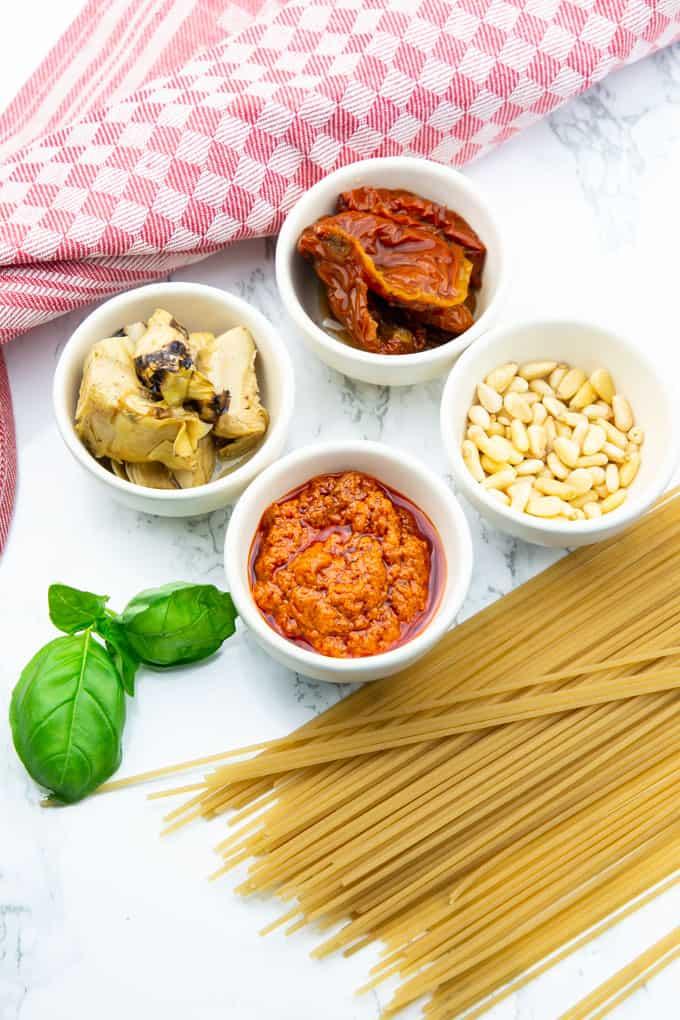 vier kleine Schüsselchen mit Pesto Rosso, getrockneten Tomaten, Artischockenherzen und Pinienkerne sowie ungekochten Spaghetti auf einer Marmorplatte