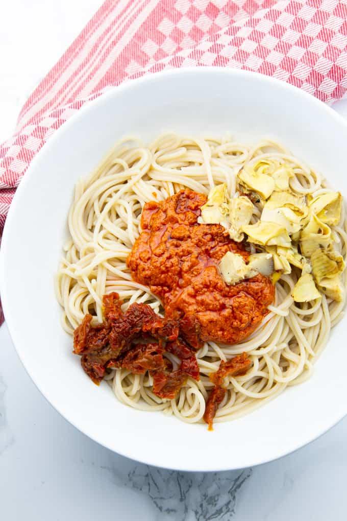 gekochte Spaghetti in einer weißen Schüssel mit Pesto Rosso, gehackten getrockneten Tomaten und Artischockenherzen auf einer Marmorplatte
