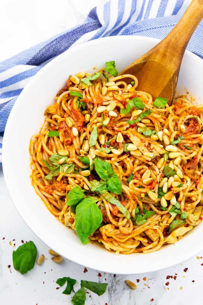 Spaghettisalat in einer weißen Schüssel mit frischen Basilikumblättern und einem Holzlöffel auf einer Marmorplatte