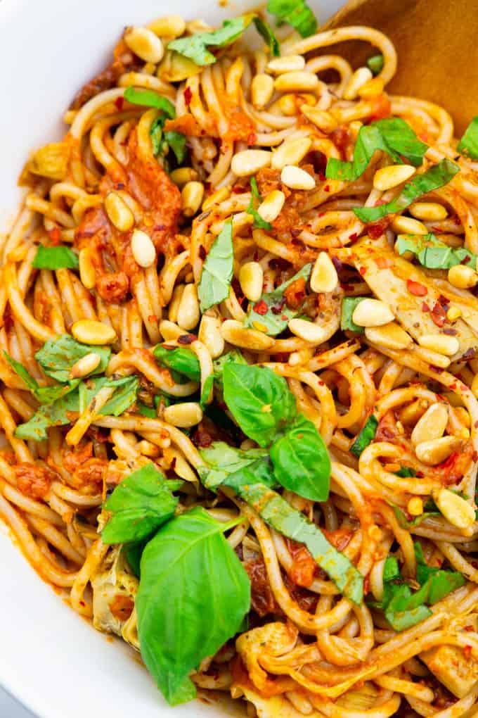 Nahaufnahme von einem Spaghettisalat in einer weißen Schüssel mit frischen Basilikumblättern