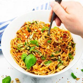 Spaghettisalat in einer weißen Schüssel mit einer Hand, die mit einer Gabel Spaghetti aufrollt