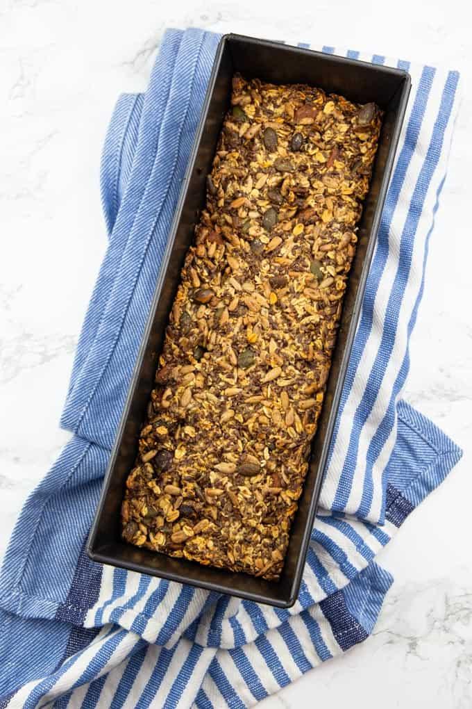 selbst gebackenes Brot in einer Brotbackform auf einem blau weißen Handtuch auf einer Marmorplatte