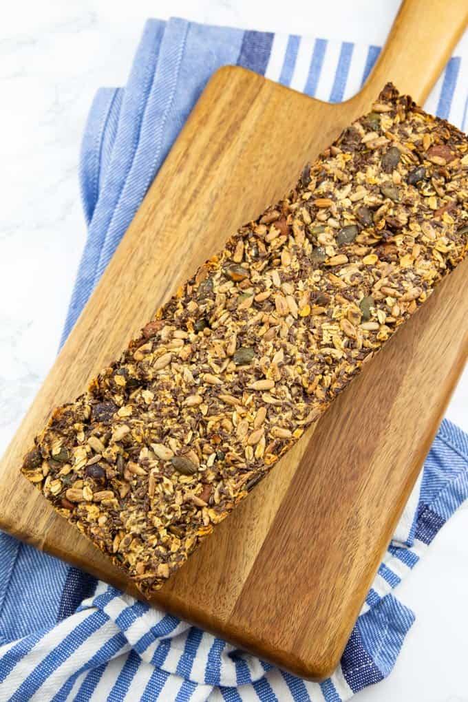 ein frisch gebackenes Brot auf einem Holzbrett auf einem blau weißen Geschirrtuch
