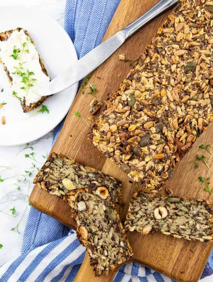 ein angeschnittenes Brot mit drei Scheiben auf einem Holzbrett mit einem weißen Teller mit einer Scheibe Brot mit Frischkäse
