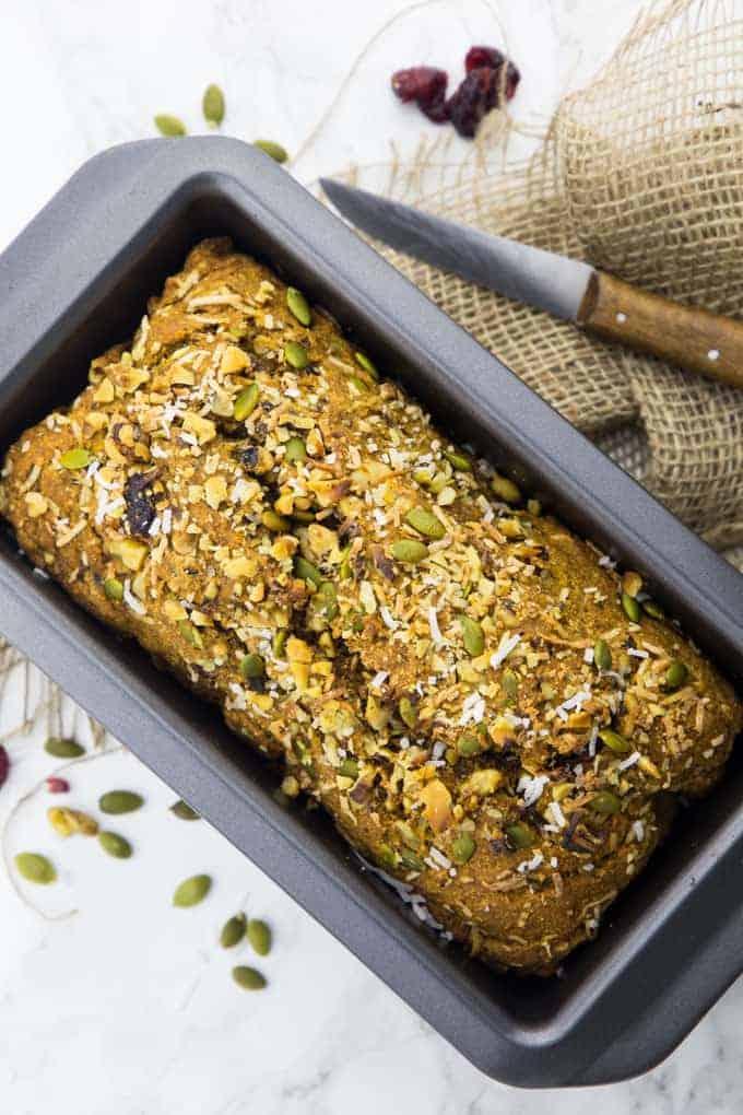 ein Kürbisbrot in einer Brotbackform auf einer Marmorplatte mit Kürbiskernen und getrockneten Cranberries auf der Seite
