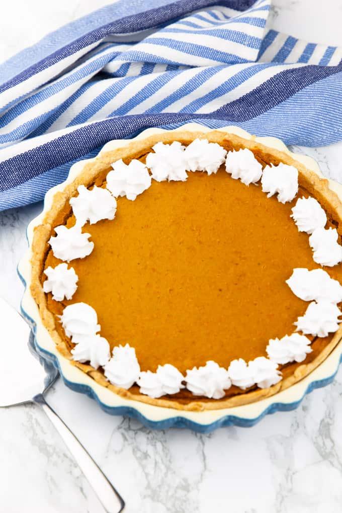 ein Kürbiskuchen in einer blau weißen Backform mit veganer Schlagsahne verziert auf einer Marmorplatte