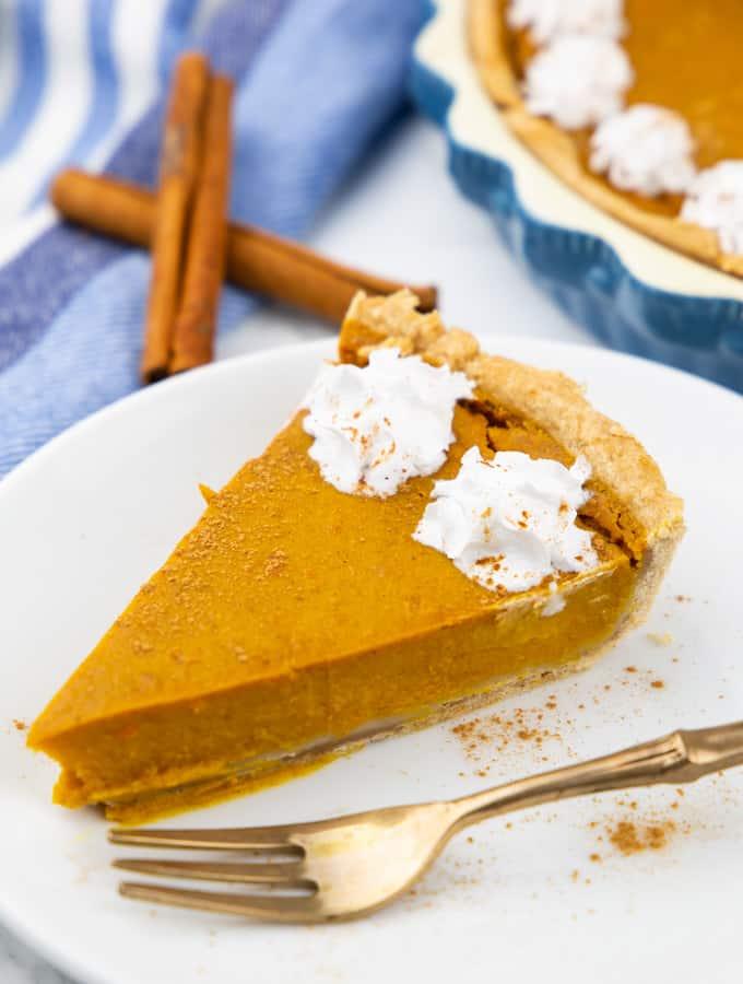 ein Stück Kürbiskuchen auf einem weißen Teller mit einer goldenen Gabel daneben