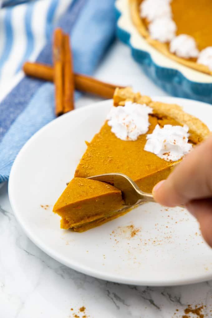 ein Stück Kürbiskuchen auf einem weißen Teller mit einer Hand, die mit einer Gabel ein Stück des Kuchens abtrennt