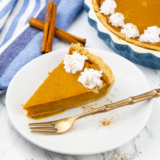 ein Stück Kürbiskuchen auf einem weißen Teller mit einer goldenen Gabel und dem restlichen Kuchen im Hintergrund