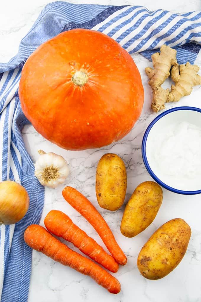 ein Hokkaido Kürbis, drei Karotten, die Kartoffeln, Zwiebel, Ingwer und Knoblauch auf einer Marmorplatte