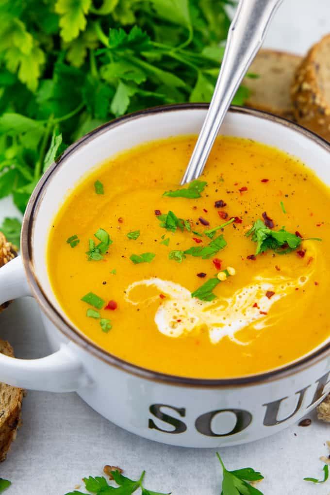 """Kürbissuppe mit Kokosmilch in einer weißen Suppenschale mit der Aufschrift """"Soup"""""""