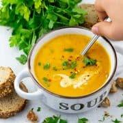 eine Suppenschüssel mit Kürbissuppe auf einer Marmorplatte mit einer Hand, die mit einem Löffel die Suppe löffelt