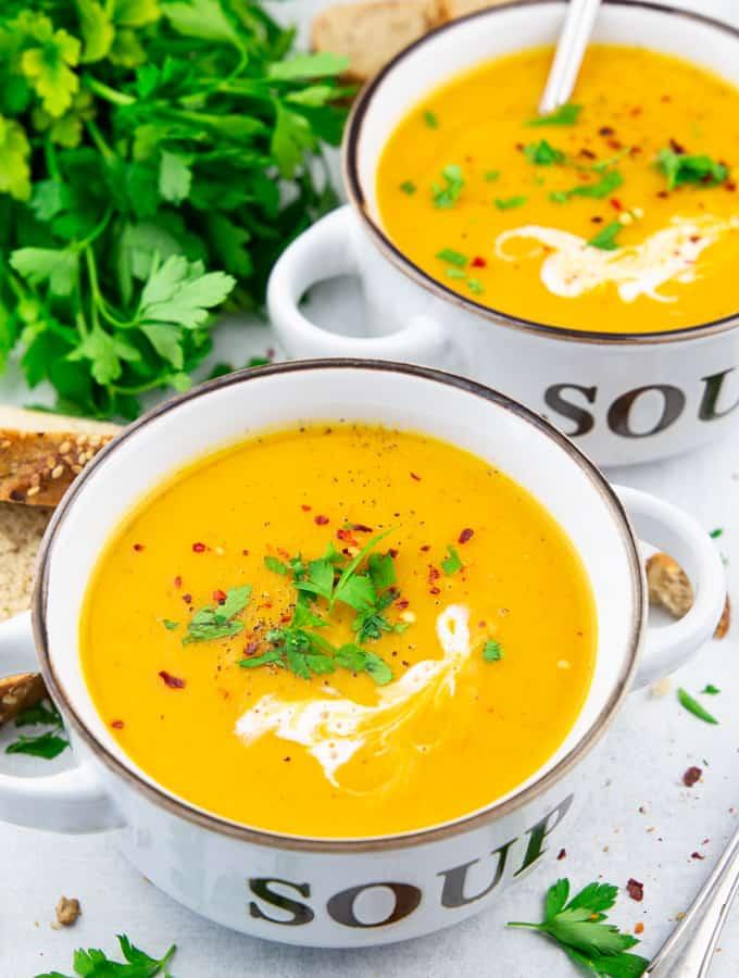 """Kürbissuppe mit Kokosmilch in zwei weißen Schüsseln mit der Aufschrift """"Soup"""" auf einer Marmorplatte"""