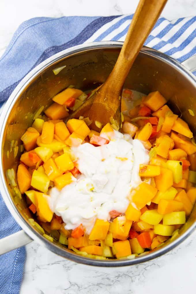 Kürbis-, Karotten- und Kartoffelwürfel mit Kokosmilch in einem Kochtopf mit einem Holzlöffel auf einer Marmorplatte