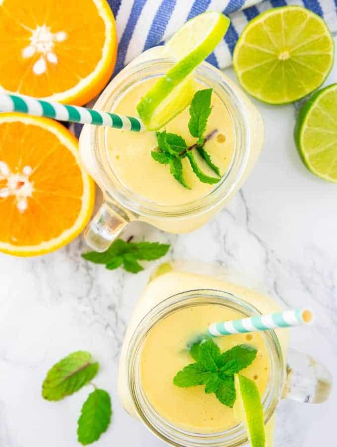 zwei Gläser Mango Smoothie mit blau weißen Strohhalmen auf einer Marmorplatte mit Orangen, Limetten und Minze Nebendran