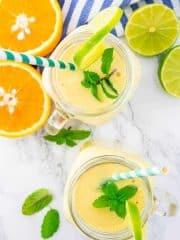 zwei Gläser Mango Smoothie auf einer Marmorarbeitsplatte mit Orangen- und Limettenhälften nebendran