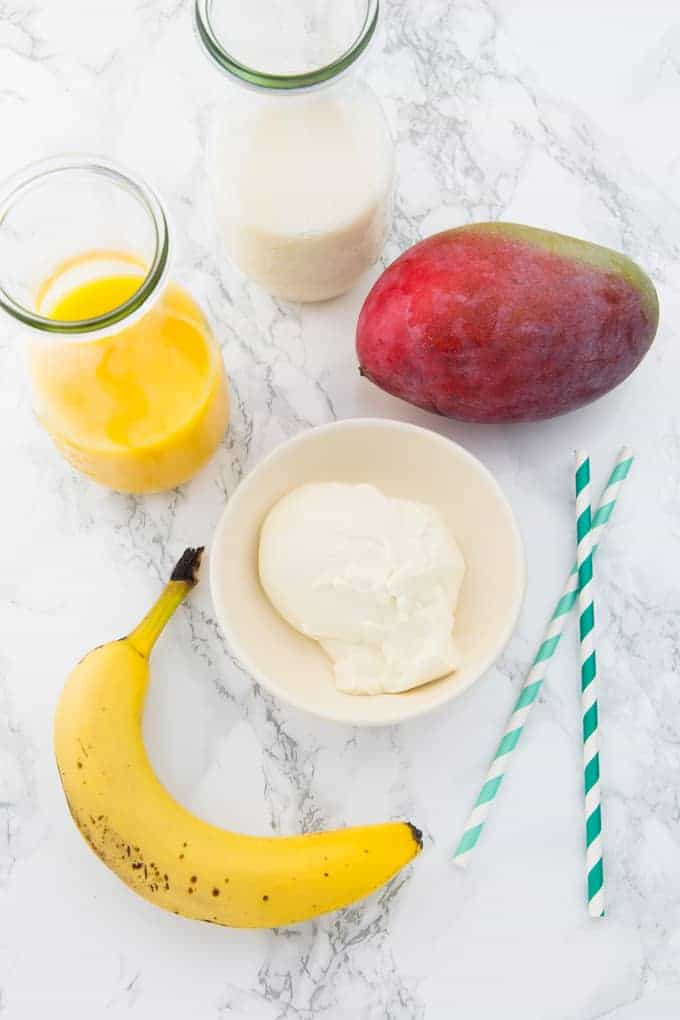 eine Mango, eine Banane, ein Schälchen mit Sojajoghurt und zwei Glasflaschen mit Mandelmilch und Orangensaft auf einer Marmorplatte