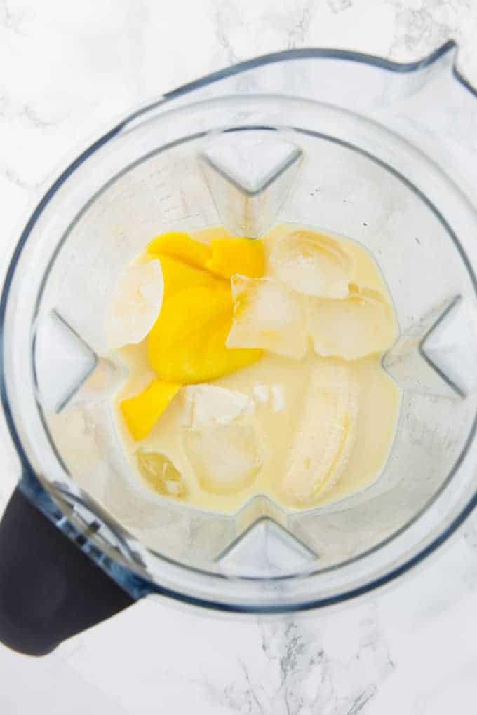 Zutaten für einen Mango Smoothie in einem Mixer auf einer Marmorplatte