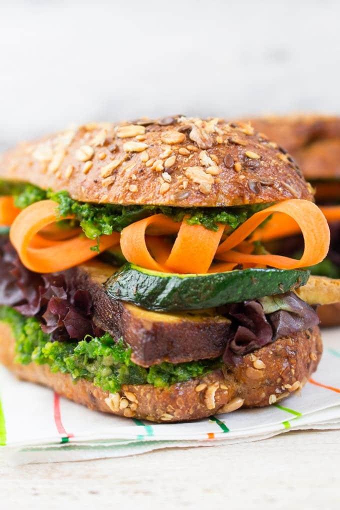 Tofu Sandwich mit Zucchini, Karotten und Pesto auf einer weißen Holzarbeitsplatte
