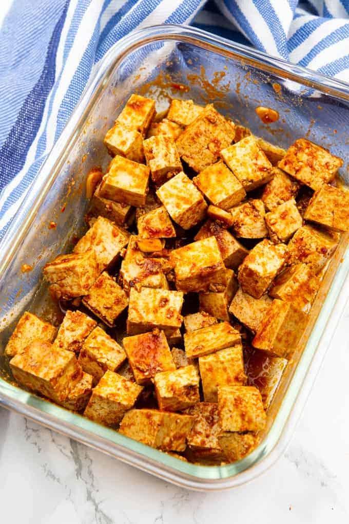 marinierte Tofuwürfel in einer Glasschüssel auf einer Marmorplatte