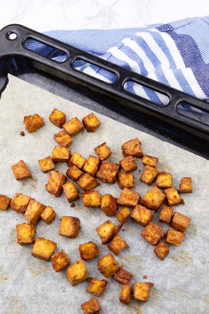 knusprige Tofuwürfel auf einem Backblech mit Backpapier
