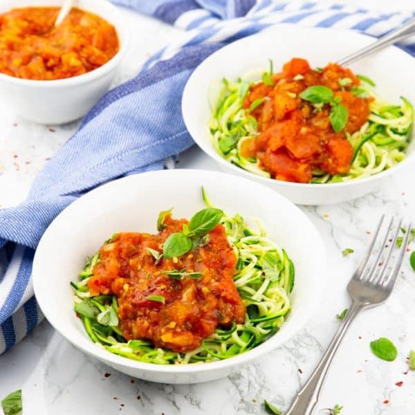 Zwei weiße Teller mit Zucchini Spaghetti und Tomatensauce auf einer Marmorplatte mit einer Gabel an der Seite