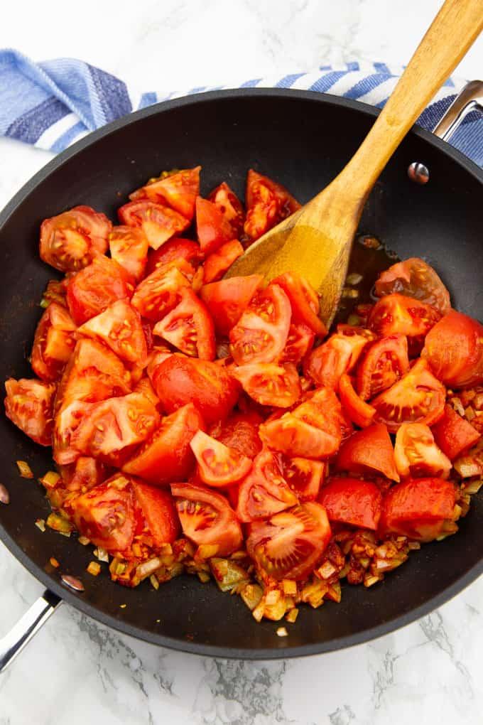 geachtelte Tomaten in einer schwarzen Pfanne mit einem Holzlöffel auf einer Marmorplatte