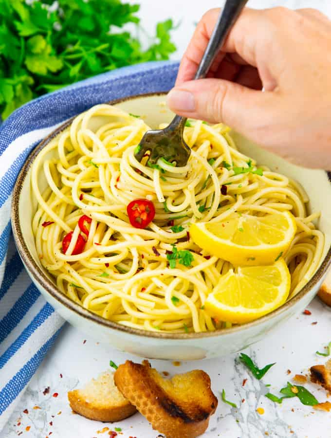 spaghetti aglio e olio in einem beigen Teller mit einer Hand, die Spaghetti mit einer Gabel aufrollt