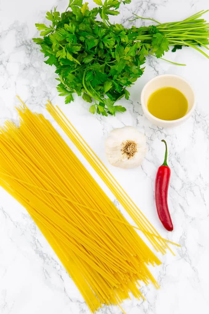 Spaghetti, frische Petersilie, Knoblauch, eine rote Chili und Olivenöl in einem kleinen Schälchen auf einer Marmorplatte