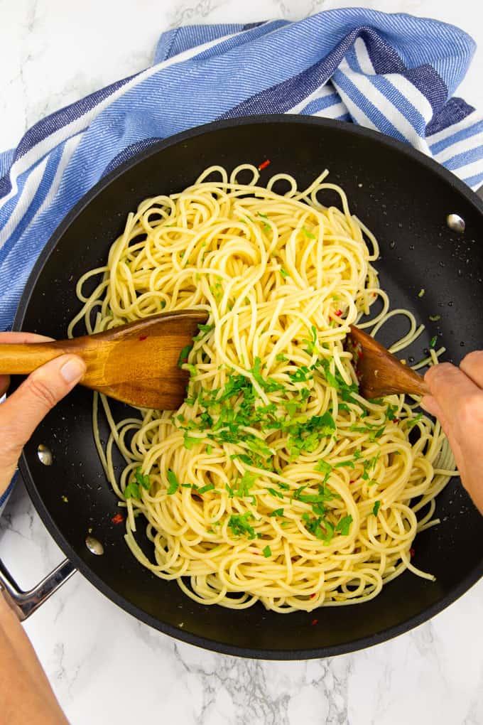 spaghetti aglio e olio in einer schwarzen Pfanne, die von zwei Händen mit Holzlöffeln umgerührt werden