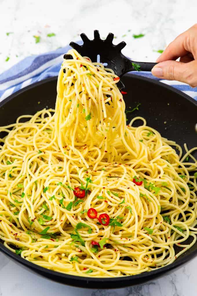 spaghetti aglio e olio in einer Pfanne mit einer Hand, die einige der Nudeln mit einer Spaghettikelle hochnimmt