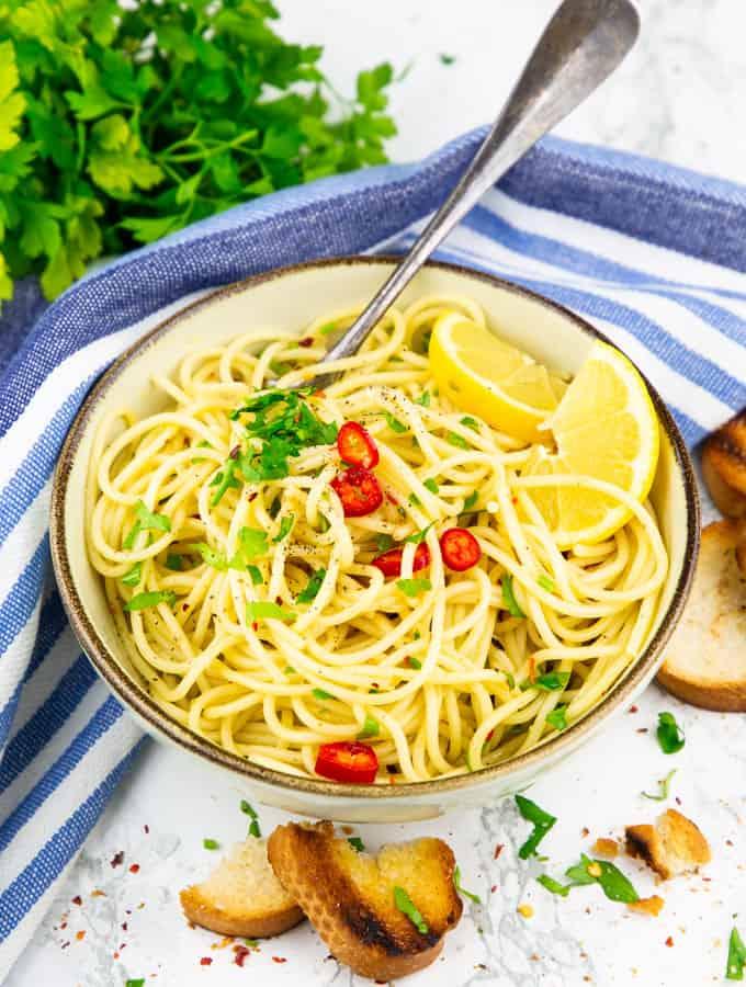 spaghetti aglio e olio in einem beigen Teller mit einer Gabel auf einer Marmorplatte mit frischer Petersilie im Hintergrund