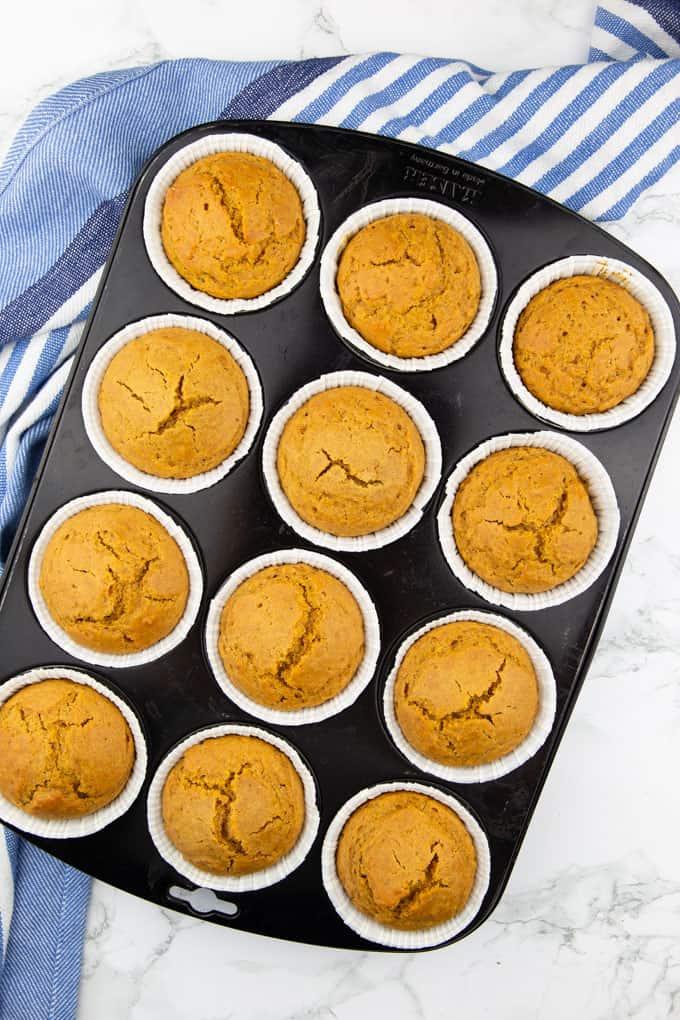 12 Kürbis Muffins in einem schwarzen Backblech auf einer Marmorplatte