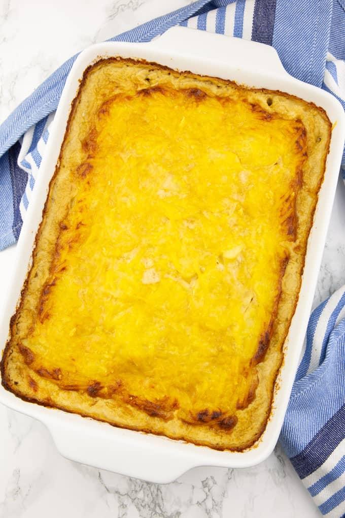 Kartoffelauflauf in einer weißen Auflaufform direkt aus dem Backofen auf einer Marmorplatte mit einem blau weißen Geschirrtuch