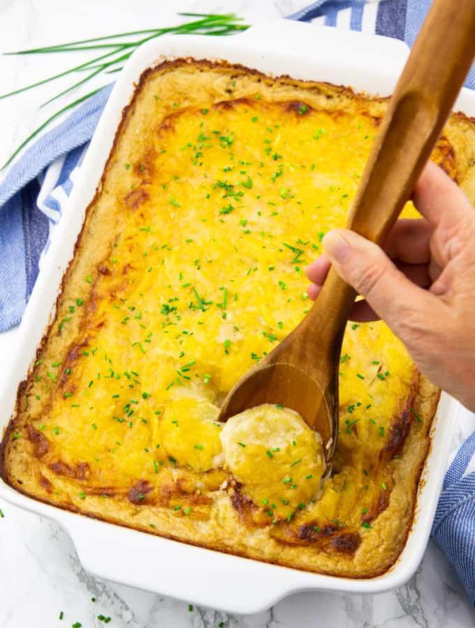Kartoffelauflauf in einer weißen Auflaufform mit einer Hand, die einen Holzlöffel hält