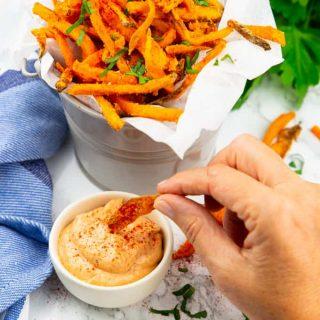 eine Hand, die eine Süßkartoffel Pommes in ein kleines Schälchen mit Dip tunkt mit mehr Süßkartoffel-Pommes in einem Eimer im Hintergrund