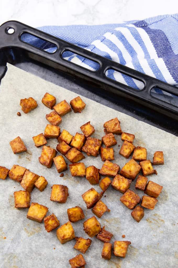 gebackene Tofuwürfel auf einem mit Backpapier ausgelegten Backblech
