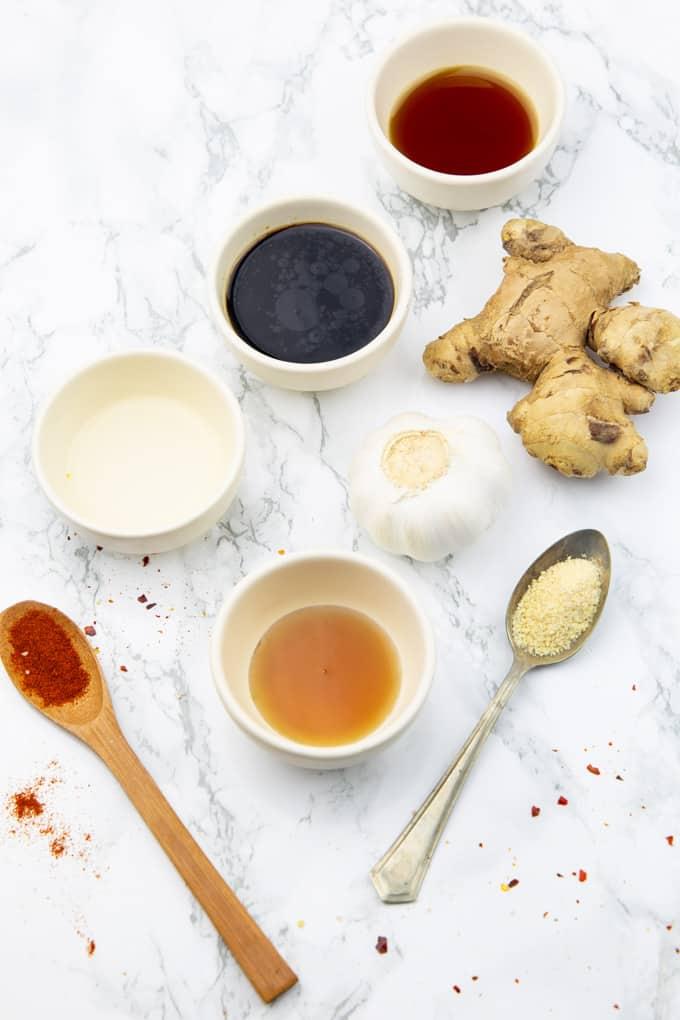 Sojasauce, Ahornsirup, Reisessig, und Sesamöl in vier kleinen Schälchen auf einer Marmorplatte mit Ingwer und Knoblauch