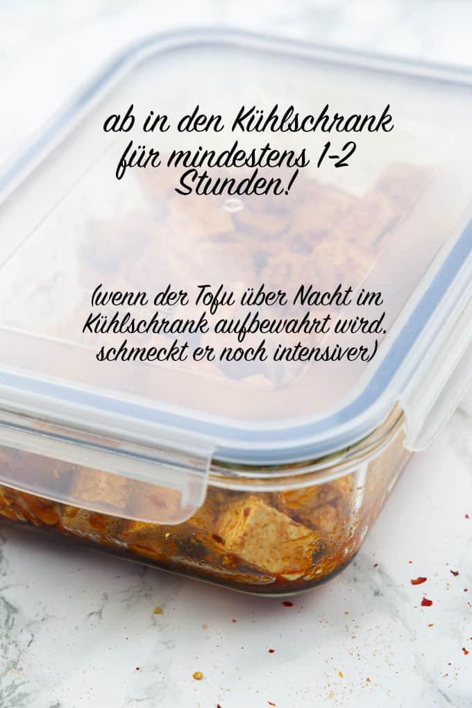 """eine Frischhaltebox mit marinierten Tofuwürfeln auf einer Marmorplatte mit der Aufschrift """"ab in den Kühlschrank für mindestens 1-2 Stunden!"""""""