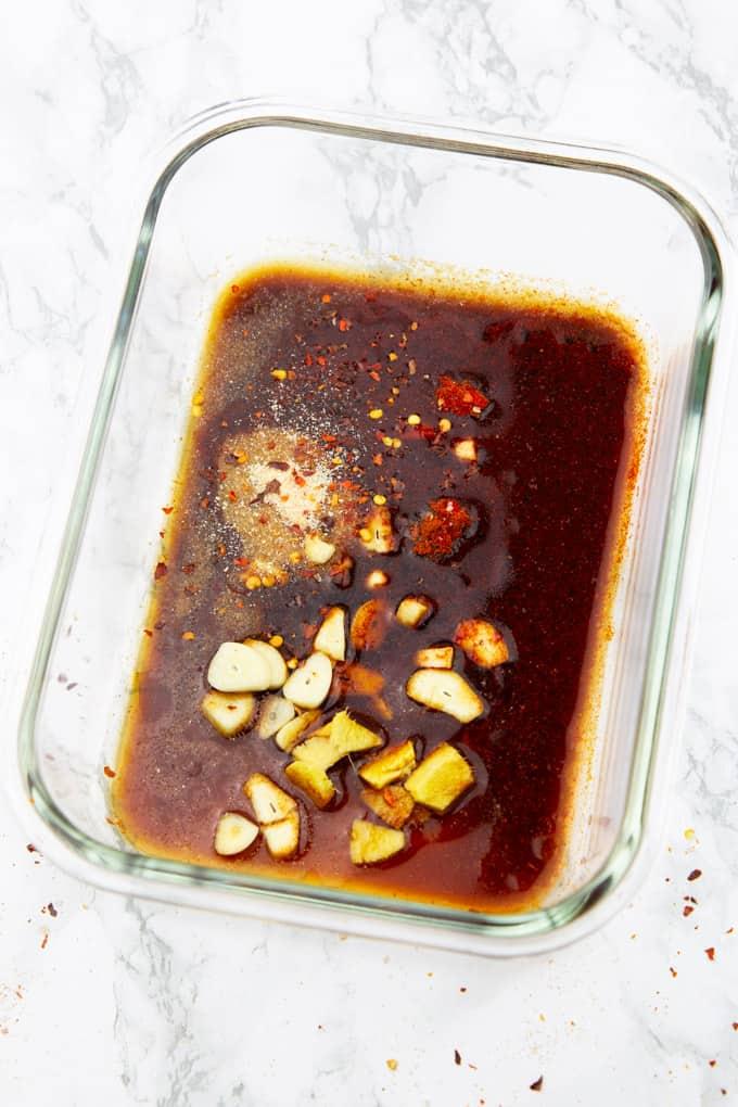 Tofu Marinade mit Knoblauch- und Ingwerscheiben in einer Glasschüssel auf einer Marmorplatte