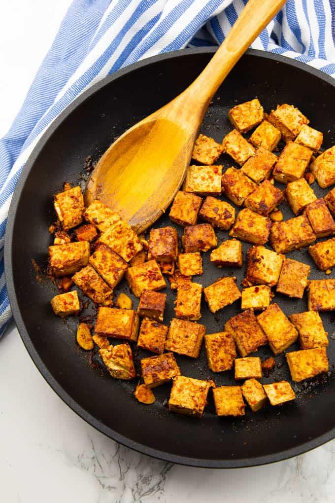 marinierte Tofuwürfel in einer gusseisernen Pfanne mit einem Holzlöffel auf einer Marmorplatte