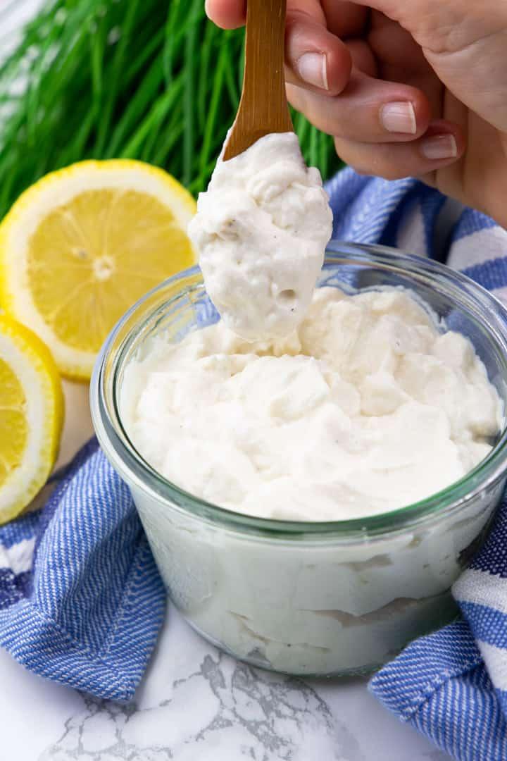 vegane Mayonnaise in einem Glas mit einer Hand, die einen Holzlöffel mit Mayonnaise hält sowie zwei Zitronen und Schnittlauch im Hintergrund