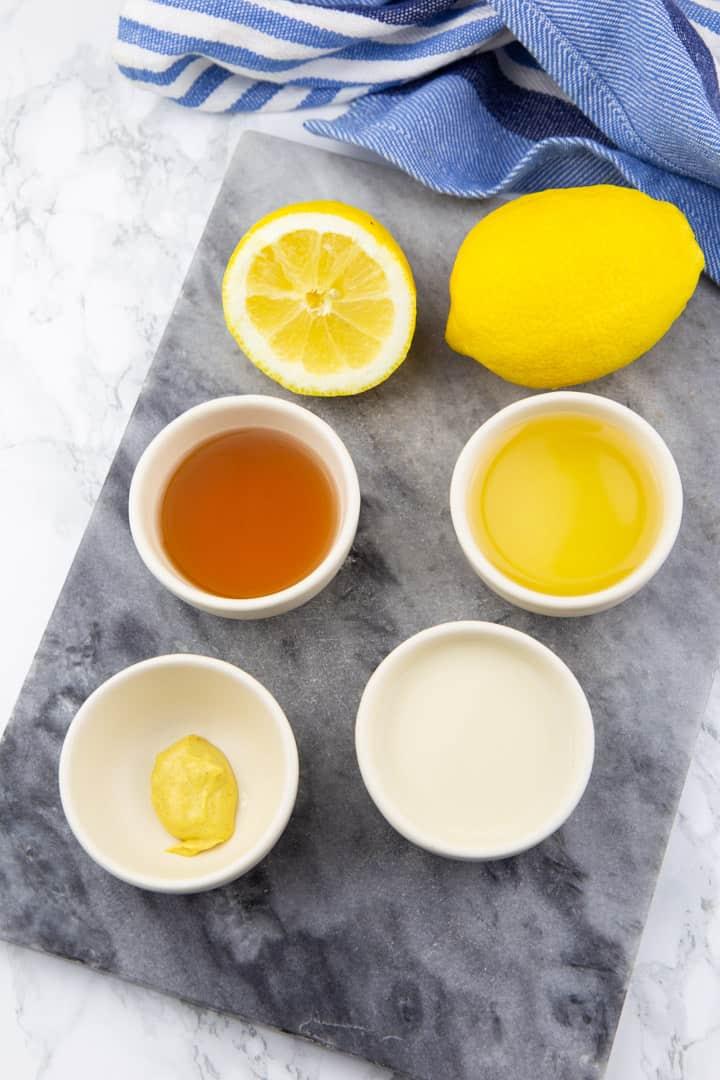 vier kleine Schälchen mit Rapsöl, Apfelessig, Sojamilch und Senf auf einer Marmorplatte